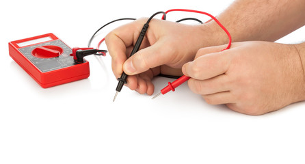 Hands and electric multimeter