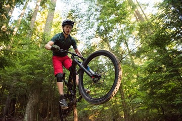 Male cyclist cycling in forest