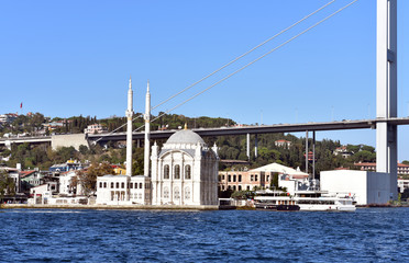 Ortakoy square and Ortakoy mosque on sunny day with the Bosphorus bridge behind