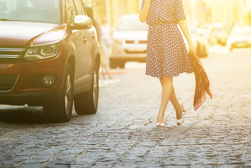 young beautiful woman in a blue sundress walking down the street next to the car, holding a sweater in his hands
