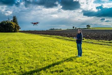 Drohne in der Luft bei Mann auf grüner Wiese