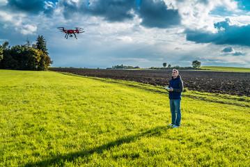 Mann auf Wiese steuert seine Drohne in der Luft