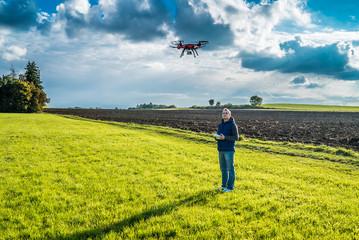 Mann mit Drohne auf grüner Wiese