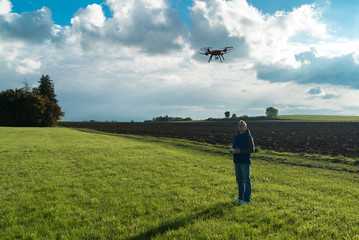 Junger Mann in idyllischer Landschaft lässt seinen Quadrocopter steigen