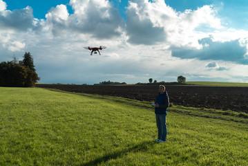 Junger Mann auf Wiese lässt seinen Quadrocopter steigen