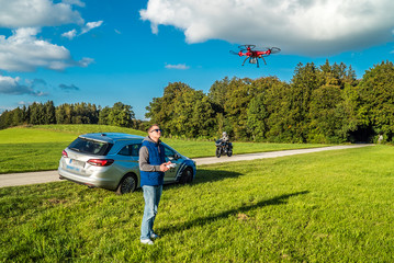 Junger Mann am Straßenrand lässt seinen Quadrocopter steigen
