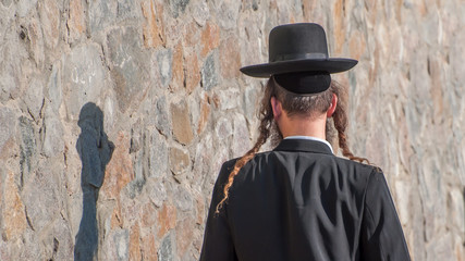 Jew Hasid ethnic headdress. Human shadow on stone wall.