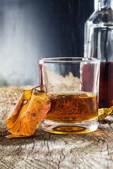 glass of whiskey with autumn leaves on the wooden table