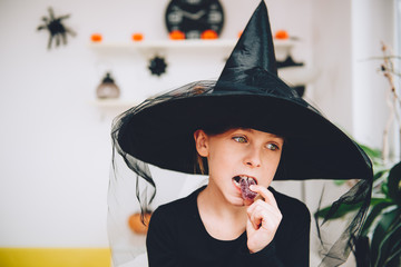Girl in Witch costume eating soft jelly candy