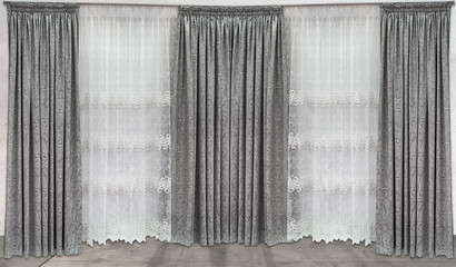 Three straight curtains made from natural material with floral ornaments and the light tulle from a...