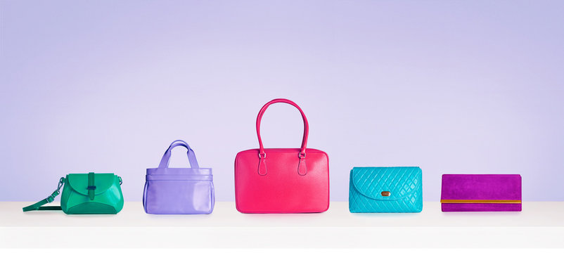 Colorful bag purse collection isolated on bright purple background.