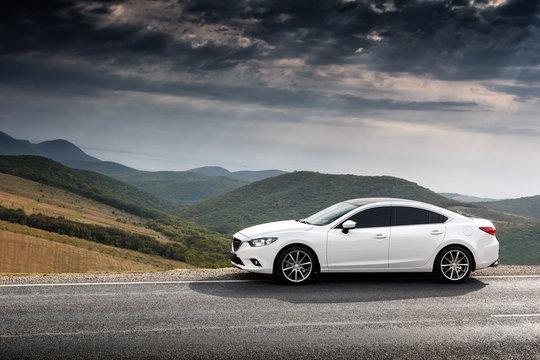 White Car parket at countryside asphalt road near green mountains at daytime