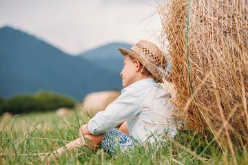 Boy sits near big hayroll on the field