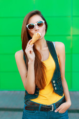 Young stylish girl eating a delicious ice cream near the green wall