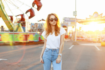 Pretty young woman with sunglasses in a white shirt and vintage jeans