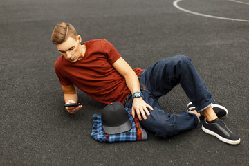 Modern handsome man uses the phone and lying on the pavement.