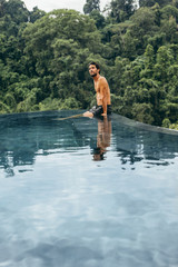 Man sitting on the edge of swimming pool