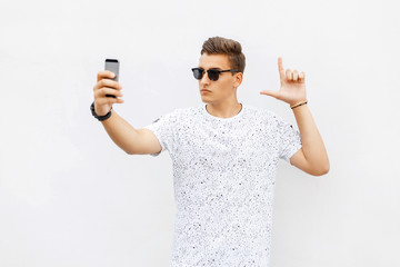Handsome man playing a game in the smartphone. Guy makes selfie
