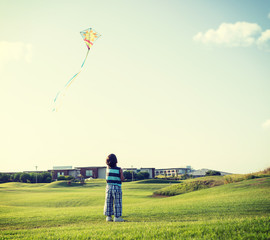 Little boy on summer vacation having fun and happy time flying k