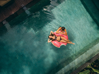 Couple relaxing on donut floatie in resort pool