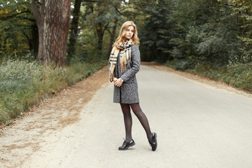 Hot model woman in vintage warm scarf in a coat and shoes walking