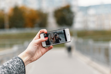 Beautiful girl with friend photographer to take photos on phone
