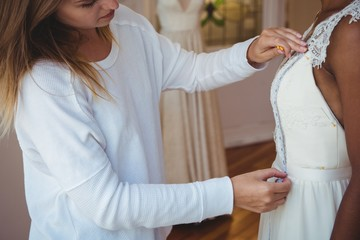 Woman trying on wedding dress with the assistance of fashion des