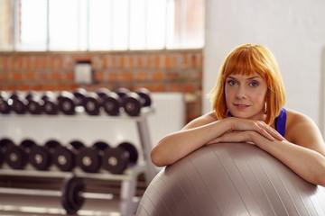 entspannte frau im fitness-studio stützt sich auf einen gymnastikball