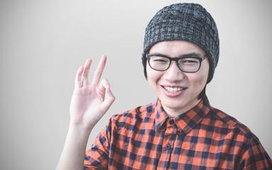 Composite image of smiling hipster making ok sign