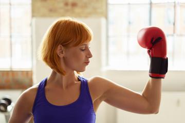 frau mit boxhandschuhen schaut auf ihre armmuskulatur