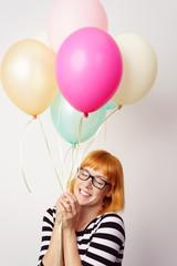 lachende frau mit ballons und geschlossenen augen