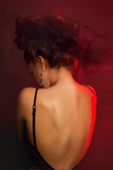 Fashion Art Portrait Of Beautiful Girl over Red lights & smoke. Closeup portrait of model posing at studio.
