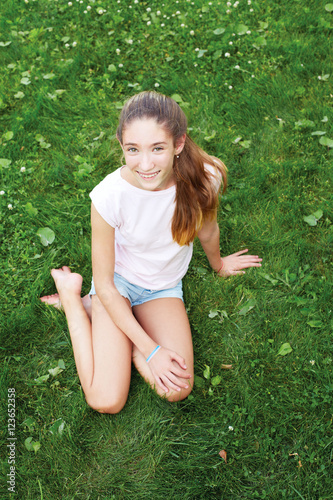 Cute Teen Girl Sitting On The Grass In The Park. She Looks Into The Camera