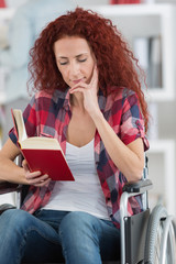 portrait of woman in a wheelchair holding a book