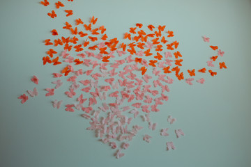 Paper pink rose and red butterflies in form of heart fly on a wall. Valentines day. 14 february