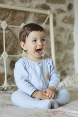 shouting baby sitting in bed with stone background