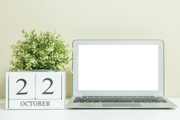 White wooden calendar with black 22 october word with white blank space at center of computer notebook on white wood desk and cream wallpaper textured background , selective focus at the calendar