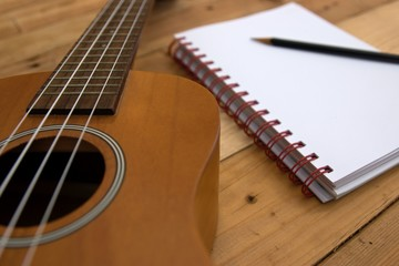 Ukulele guitar Notebook and pencil on wood table