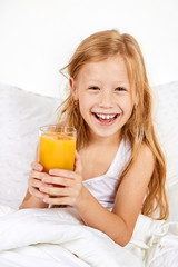 Portrait of happy little girl with glass of juice