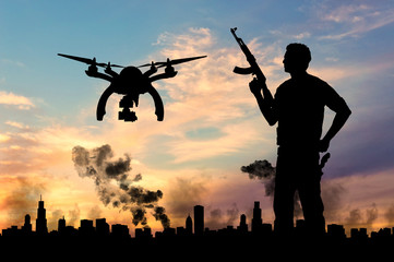 Silhouette flying reconnaissance drone over city in a smoke and a terrorist