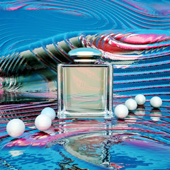 Perfume in a glass bottles and pearl beads on a color background
