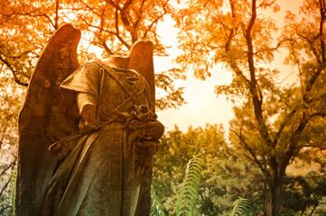 Graveyard scene: headless statue among autumn trees