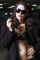 Closeup portrait of beautiful smoking young girl in underwear and coat