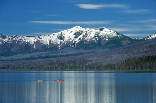 Kayaking by snow covered mountains in Glacier National Park Montana