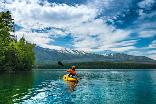 Kayaking in the spring by snow covered mountains on Lake McDonald in Glacier National Park Montana
