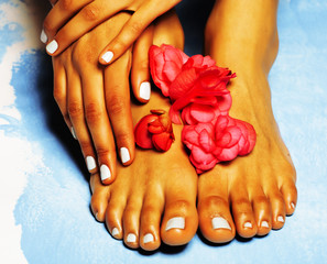african Female feet and hand, blue pedicure with pink flower