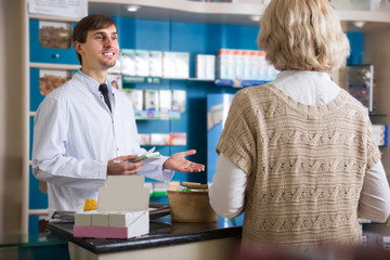Male pharmacist talking to customer at pharmacy