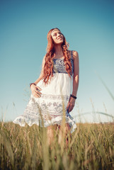 Smiling pretty hippie woman standing in the meadow
