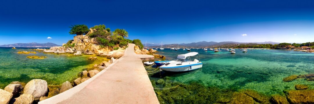 Corsica island with palm trees, tourquise clear water and yacht