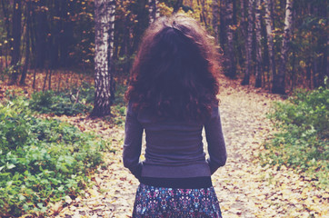 Girl with dark curly hair into the autumn wood